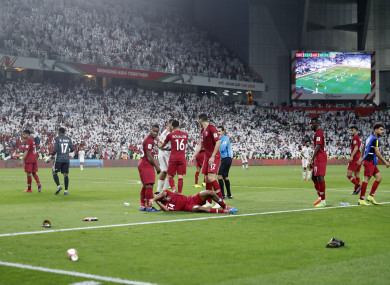 Qatar defender Salem Al Hajri lies on the ground after shoes and bottles are thrown in by United Arab Emirates fans.