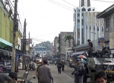 Soldiers and police cordon off the area after two bombs exploded outside a Roman Catholic cathedral in the Philippines.