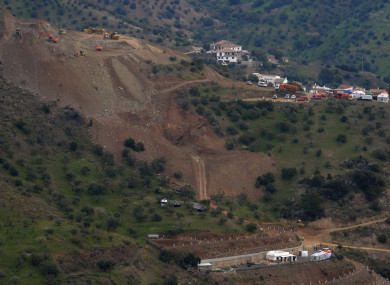 Drill machines and excavating machinery work on top of the mountain, top left, next to a deep borehole to reach a 2-year-old boy trapped there for six days near the town of Totalan in Malaga