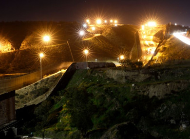 Floodlights from the US illuminate multiple border walls in Tijuana, Mexico.