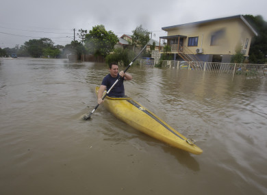 A man kayaking in flood waters in Hermit Park Townsville, Australia.