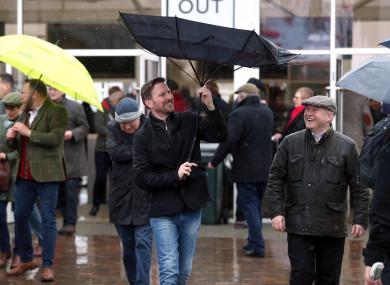 A racegoer adjusts his umbrella at Cheltenham.