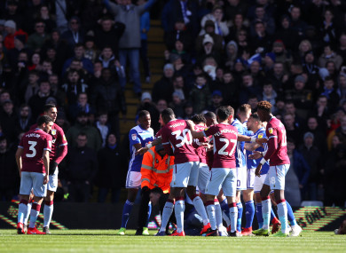 Aston Villa players swarm around Jack Grealish after he is punched by a fan.