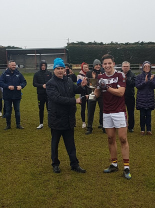Gerry Tully presents the Corn Daithi Billings to NUIG captain Evan O'Brien.