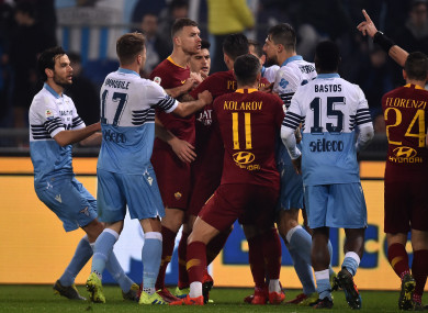 Edin Dzeko of AS Roma argues with Lazio players during the game.