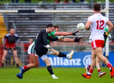Niall Morgan kicks a score against Mayo under pressure by Aidan O'Shea.
