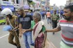 Sri Lankan elderly woman is helped near St. Anthony's Shrine after a blast in Colombo
