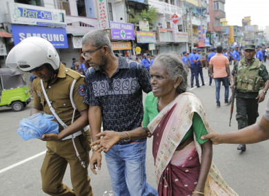 Sri Lankan elderly woman is helped near St. Anthony's Shrine after a blast in Colombo