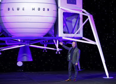 Amazon founder Jeff Bezos speaking in front of his model Blue Moon lunar lander