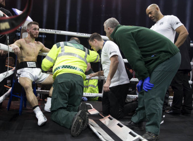 Burnett receives medical treatment in his corner after retiring with a back injury against Nonito Donaire.