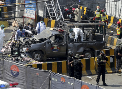Pakistani security personnel surround a damaged police van in Lahore