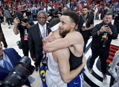 Steph Curry, right, hugs his brother Seth - who plays for Portland - after Golden State's win.