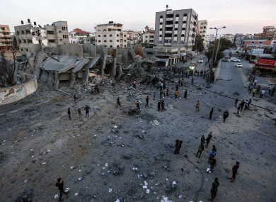 Palestinians inspect the remains of a building that was destroyed during Israeli airstrikes.