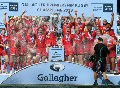 Saracens players lift the trophy following victory.