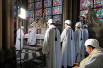 The Archbishop of Paris Michel Aupetit, second left, leads the first mass in a side chapel, two months after the fire at Notre Dame.