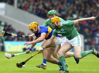 Tipperary's Ronan Maher is tackled by Limerick's Seamus Flanagan and Shane Dowling.