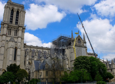 A statue is removed from Notre-Dame de Paris after April's fire.