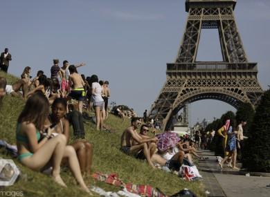 People enjoy the sun on the Trocadero gardens near the Eiffel Tower in Paris, Friday,