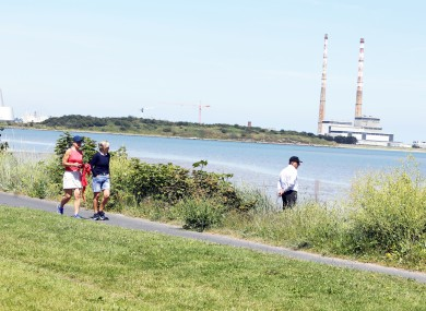 People walking in the sun on Sandymount Strand in Dublin in good weather this week