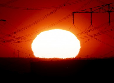 The sun rises near power lines in Frankfurt, Germany.
