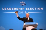 Boris Johnson waves a fish during a Tory leadership hustings in London