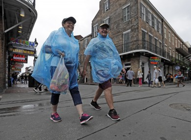 Alan and Dot Richardson wear ponchos as they walk along Bourbon Street in the French Quarter in New Orleans.