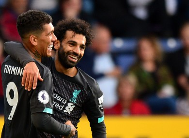Firmino and Salah celebrate Liverpool's third goal.