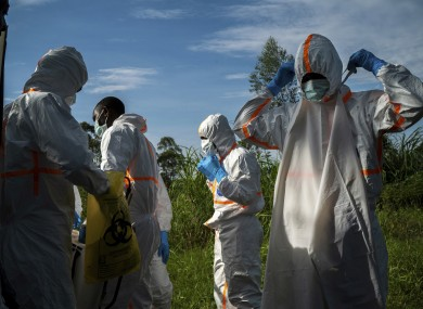 Burial workers put on protective gear before carrying the remains of a man who died from Ebola
