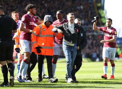A supporter is escorted away after attacking Grealish.