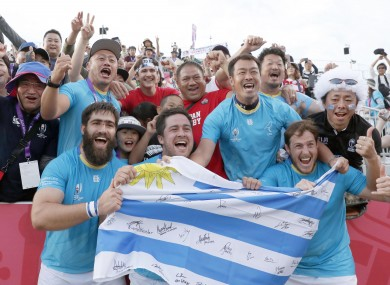 Uruguay players celebrate with supporters in Kamaishi.