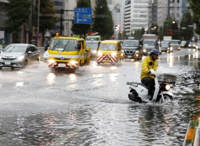A man rides a moped through a flooded street due to a typhoon in Tokyo