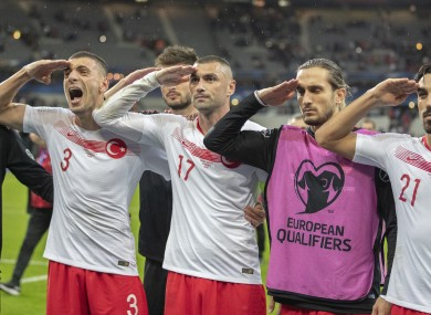 Turkey players celebrate with a military salute.
