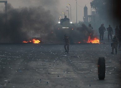 Iraqi security forces fire tear gas to disperse anti-government protesters in Baghdad, Iraq.