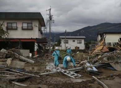 Electricity workers survey damages in a neighborhood devastated by Typhoon Hagibis