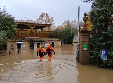 Rescue workers in a flooded street in southern France yesterday.