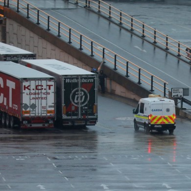 A garda van approaches a ferry where up to 16 people were found alive in a truck en route to Rosslare