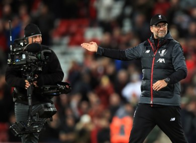 Jurgen Klopp gesutres to a television camera after a league game with Tottenham.