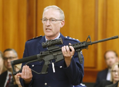 Police acting superintendent Mike McIlraith shows New Zealand lawmakers an AR-15 style rifle similar to one of the weapons a gunman used.