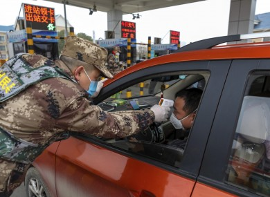 A security guard tests a driver's temperature at a checkpoint at a highway toll gate in Wuhan on Thursday
