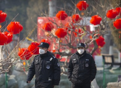 Officials wearing face masks among decorations for the Chinese New Year.