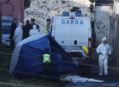 A tent is placed in front of the burnt out car in Ballybough, where remains were discovered yesterday.