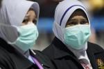 Health officials wear face masks at Kuala Lumpur International Airport in Malaysia.