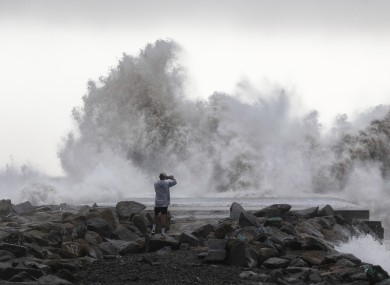 A man takes a snapshot of the waves hitting the breakwater in Barcelona, Spain