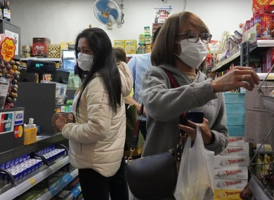 People wear protective face masks as they make purchases from a convenience store in Hong Kong.
