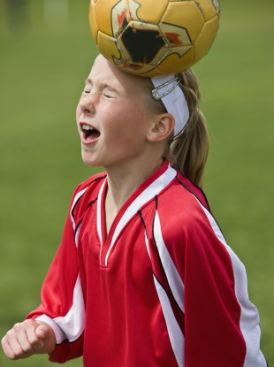 A young girl heads a football.