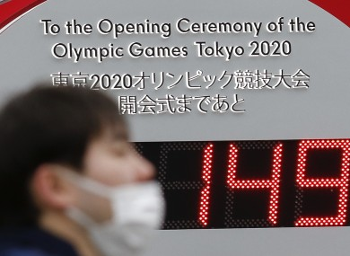 A man wearing surgical mask walks past a countdown clock outside Tokyo Station for the opening ceremony of the Tokyo 2020 Olympic and Paralympic Games.