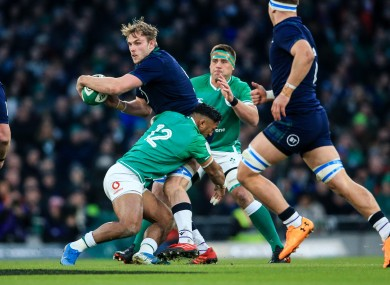 Jonny Gray looks to offload from a tackle by Ireland's Bundee Aki.