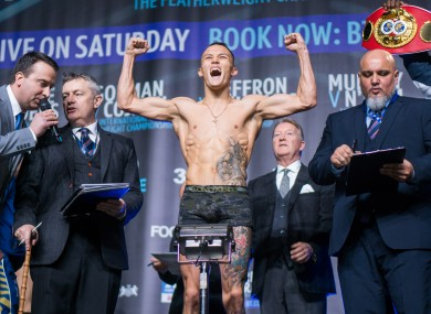 Promoter Warren looks on as Warrington weighs in for his world-title defence against Carl Frampton.