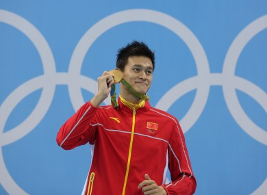 Sun Yang holding up his gold medal for the men's 200m freestyle at the Rio Olympics.