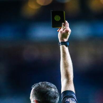 Referee Sean Hurson issues a black card during a football league game.